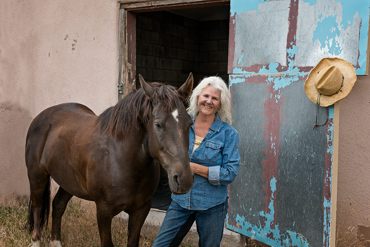 Horses woman standing with horse in front of metal door photographed by Cate Goedert Santa Fe pet photographer
