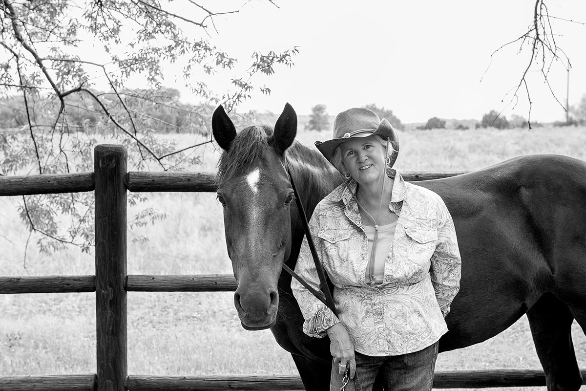 Horses black and white portrait of woman leaning against horse photographed by Cate Goedert Santa Fe pet photographer