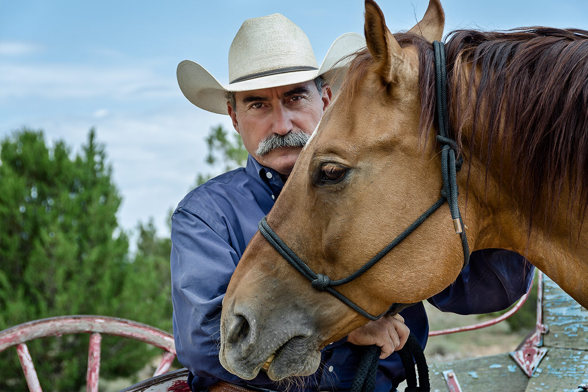 Horses man in white hat standing behind horse photographed by Cate Goedert Santa Fe pet photographer
