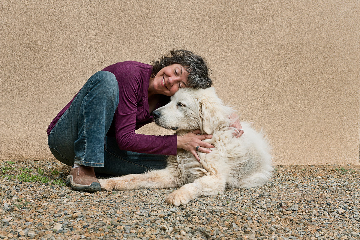companions portrait of woman holding Great Pyrenees dog by Cate Goedert Santa Fe New Mexico pet photographer