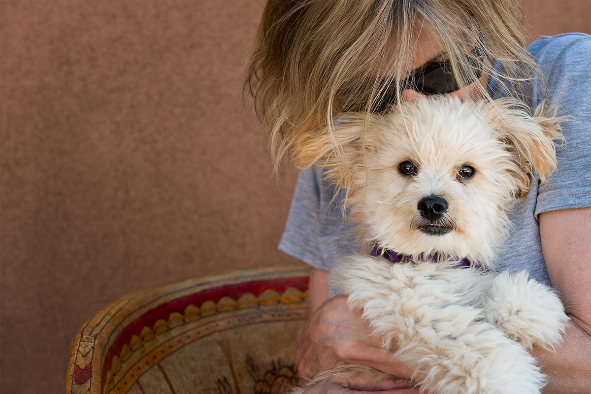 companions portrait of woman cuddling puppy by Cate Goedert Santa Fe New Mexico pet photographer