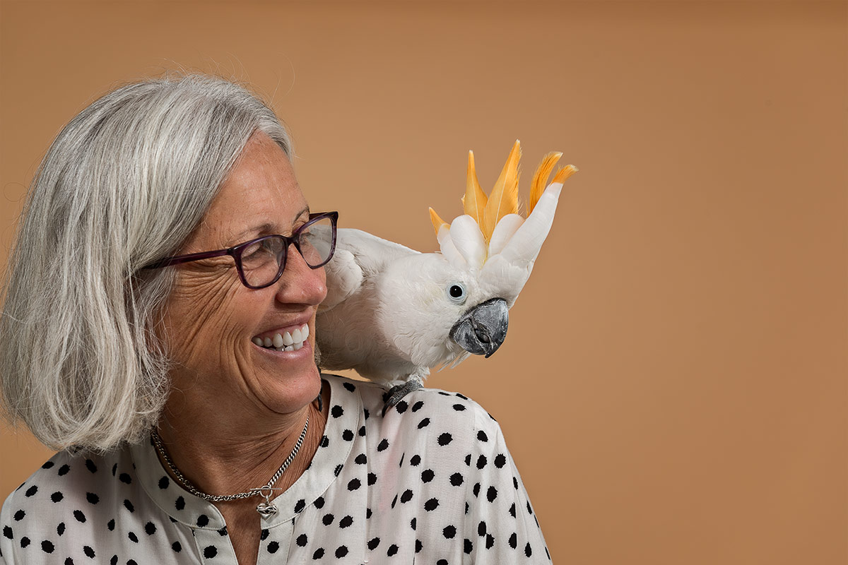companions portrait of cockatoo bird sitting on woman's shoulder by Cate Goedert Santa Fe New Mexico pet photographer